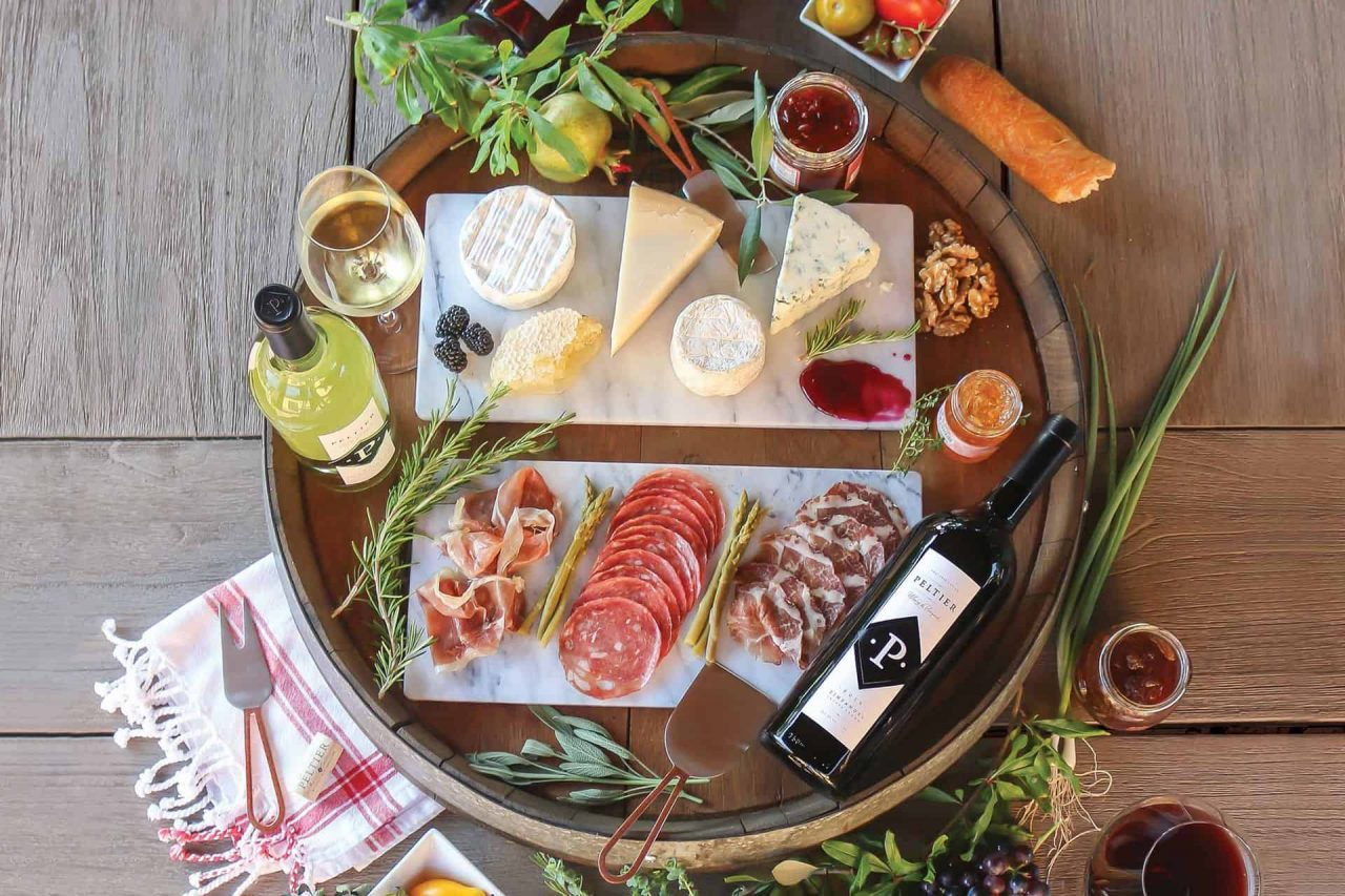 A photo from above of a charcuterie board on a wood table with a bottle of red, white and rosé wine