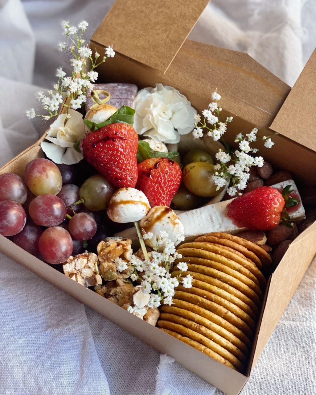 cheese box with fruit, crackers and flowers