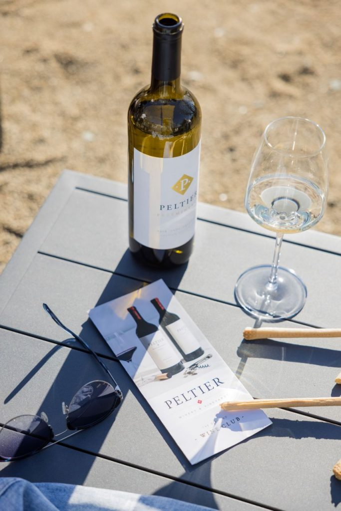 wine club brochure on table with wine breadsticks and sunglasses