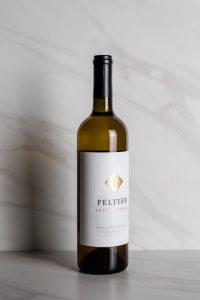 2018 Premium White Blend Prééminence bottle in front of white marble background