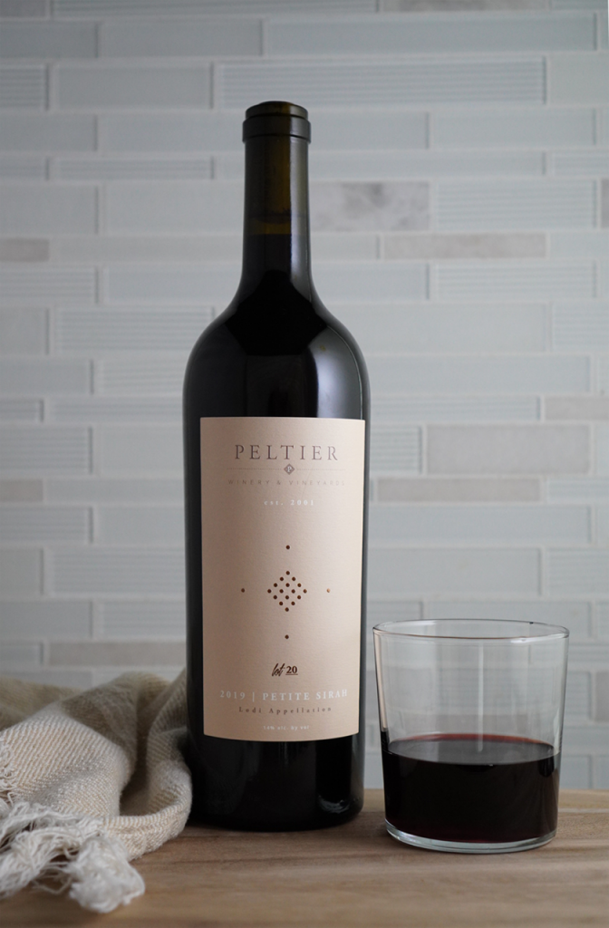 Bottle of Petite Sirah on counter with glass of red wine and tan towel