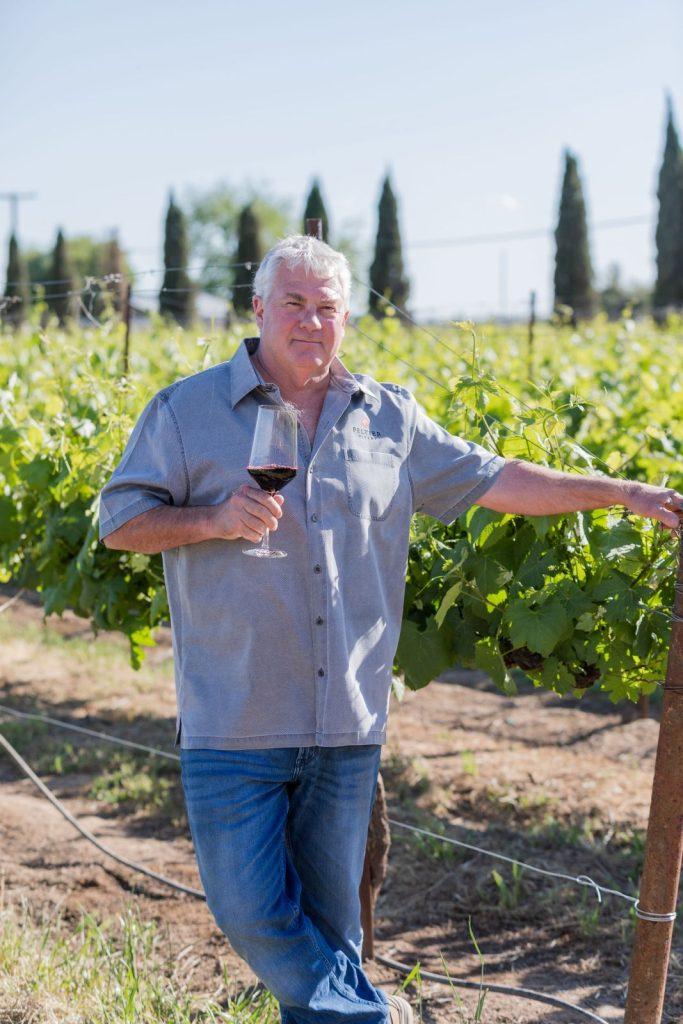 Peltier proprietor Rod Schatz, standing in the vineyard holding a glass of red wine