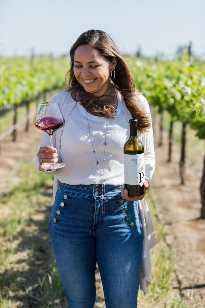 Woman smiling and swirling a glass of red wine in vineyard, holding a bottle
